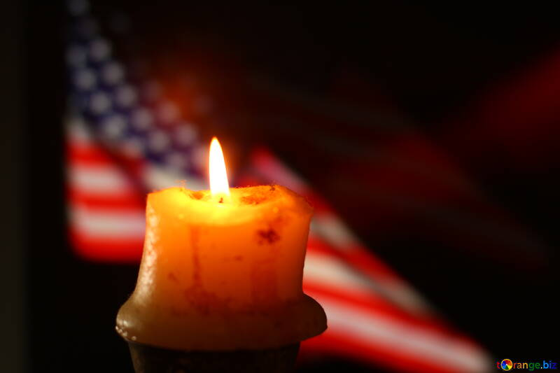 A candle with a flame in front of an american flag №52487