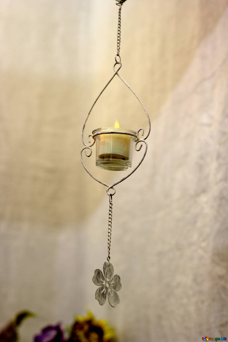a candle hanging from a wall with a flower chain hanging below Candle lantern wire hearts with Hanging container №52820