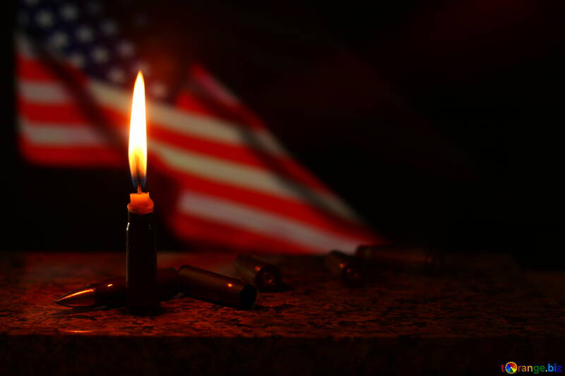 A burning candle with an American flag behind it bullets on whatever wood the candle is on United States №52527