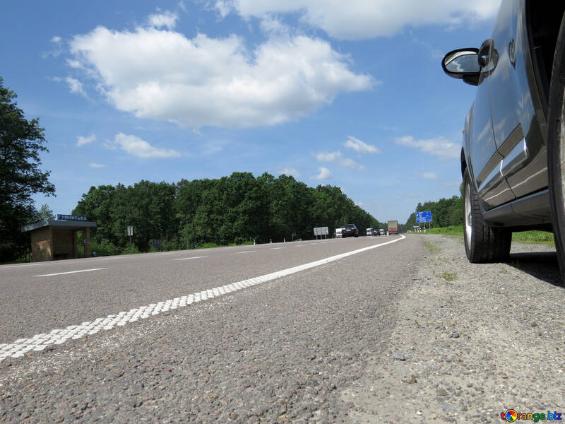 Low angle view of asphalt road, the side of a car on the right, trees at the horizon, blue sky with large cloud №52028