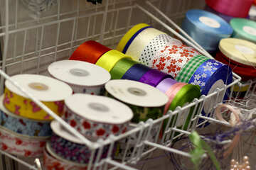 Rolls of ribbon in a wire basket colorful and patterned tape spools №53119