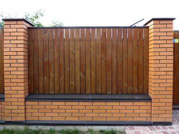 Brown fence in between two brick walls bricks gate №53434
