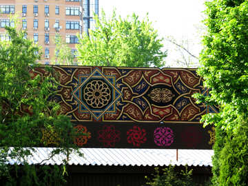 a bridge railing or canopy above a store with beautiful deisgn, trees and building in the distance art billboard №53366