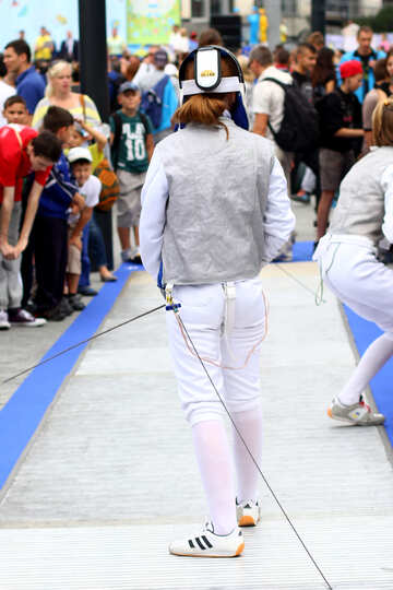 Girl wearing white Adidas shoes seemingly performing in front of an audience fencing №53989
