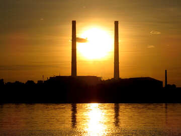 Smokestacks sun setting over an island sunset №53471