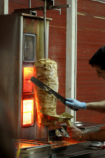 a hand cutting meat off a stick with meat Schwarma doing barbecue kebab cooking №53553