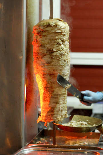 cooking shawarma it seems Chicken  kebab cooking hand with scraping tool Cook and shop advertisem №53554