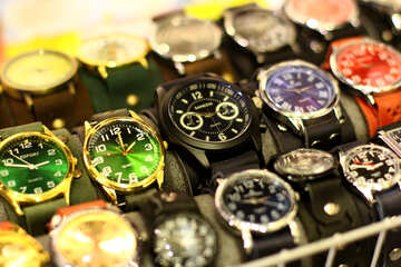 A group of different coloured watches on display
