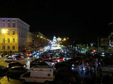 Edificios con autos y personas en una calle iluminada por las luces nocturnas de la ciudad №54107
