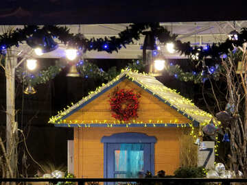 Рождественский желтый дом с голубыми вставками и желтыми огнями, на заднем плане - гирлянда с синими колокольчиками. №54060
