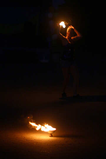 person standing over fire in darkness №54380