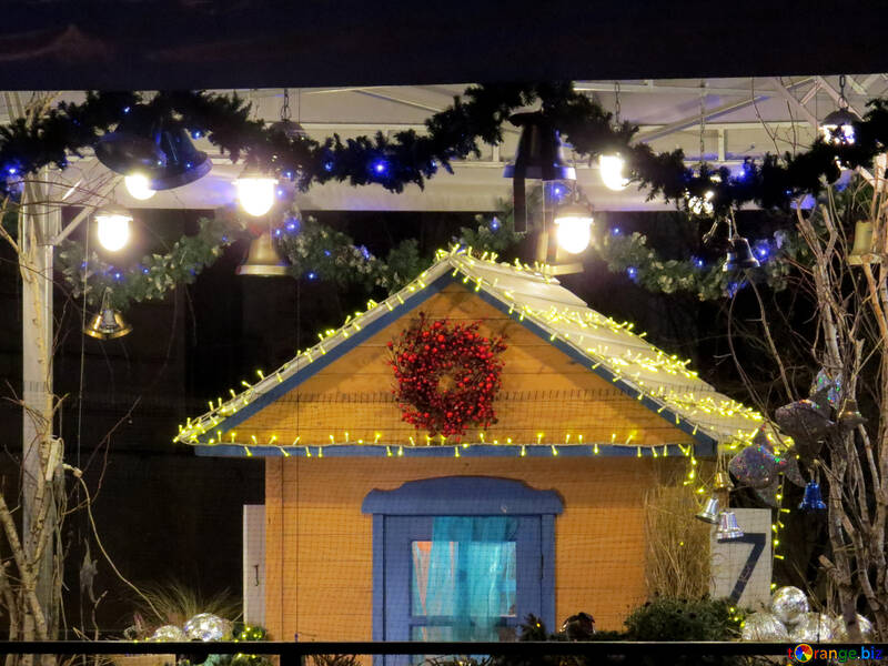 Christmas yellow house, with blue accents and yellow lights, with a garlend in the background with blue bells. №54060